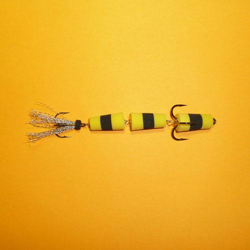 Приманка Джиг. Флажок 130 Жел./чер./жел.Джиговые (мандула)<br>Приманка джиг. ФЛАЖОК 130 жел./чер./жел. Модель <br>№130/2 тройника/ классика, судаковая/уп. 5шт. <br>Модель №130 – 3-х-секционная приманка с двумя <br>тройниками, предназначенная в первую очередь <br>для судака, когда он предпочитает некоего <br>«червячка». Отличается она и игрой – виляет <br>хвостиком, что особенно заметно при медленной <br>проводке. Практика показала, что и крупная <br>щука также не прочь полакомиться приманкой <br>несколько большего размера. Применяется <br>в незакоряженных водоемах. Тройники №1/0 <br>Kumho и №4 Sung-Woon (Корея).<br><br>Сезон: Летний